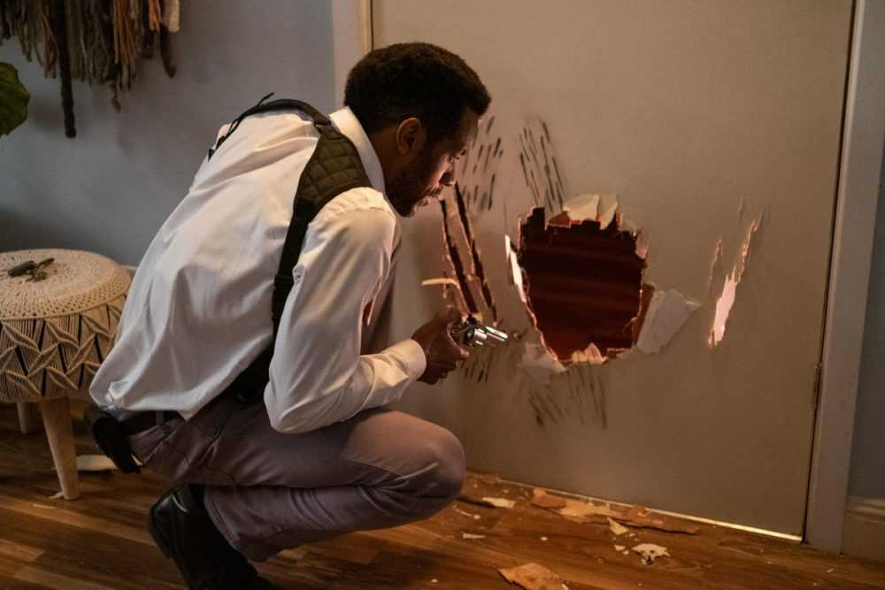 Nate (McKinley Freeman)examines scratch marks and a hole in a door