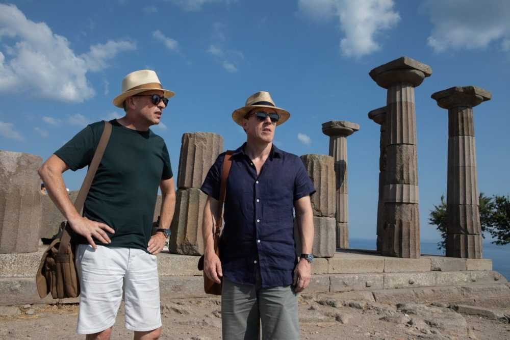 the two men stand among a set of columns