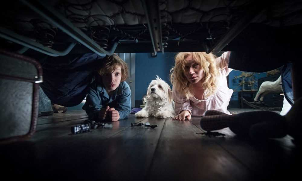 Essie Davis and Noah Wiseman peer under the bed, checking for monsters in The Babadook.