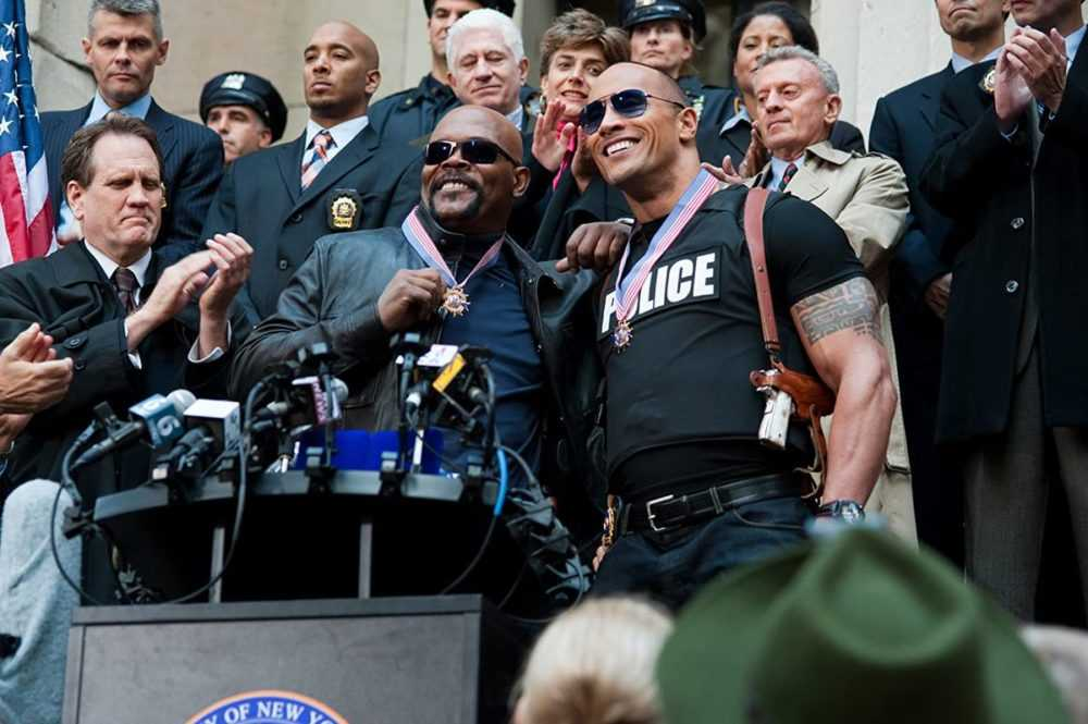 The Rock and Samuel L. Jackson stand in front of a podium
