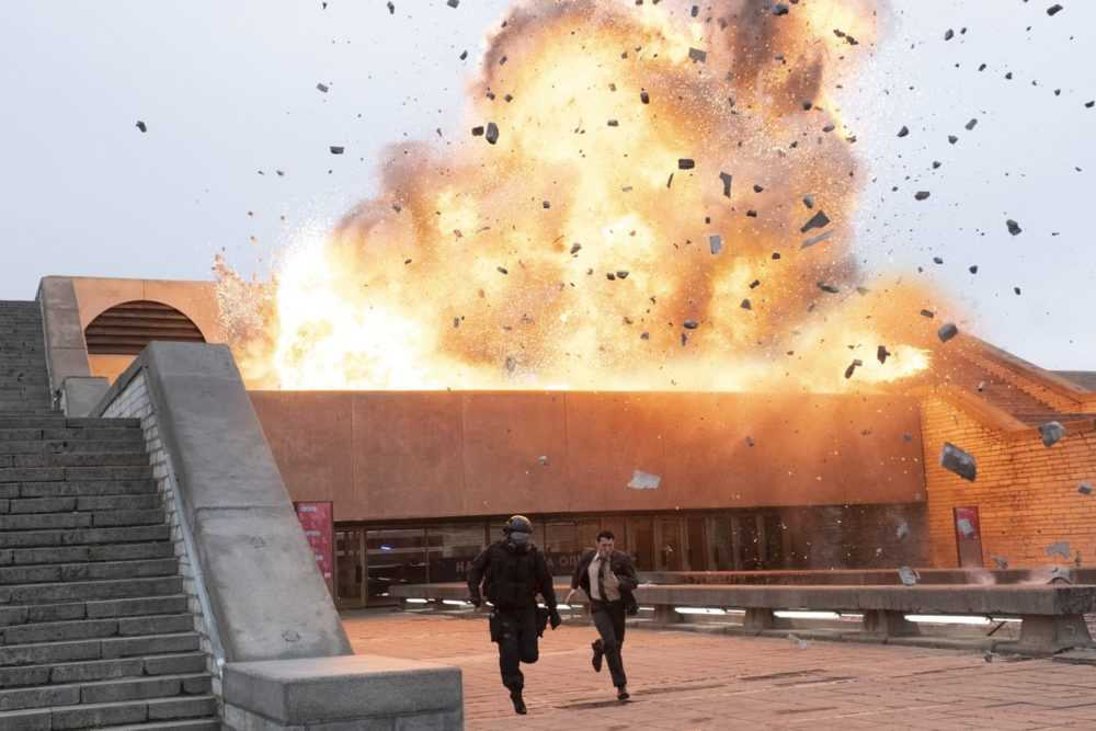 Characters run from an exploding building in Tenet
